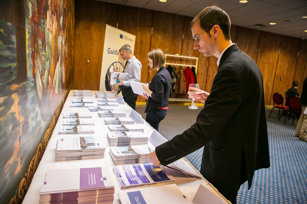 Event participant looking at fi-compass publications